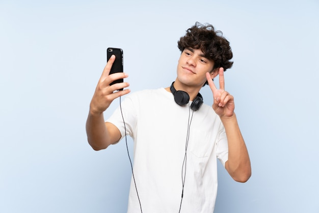Young man listening music with a mobile over isolated blue wall