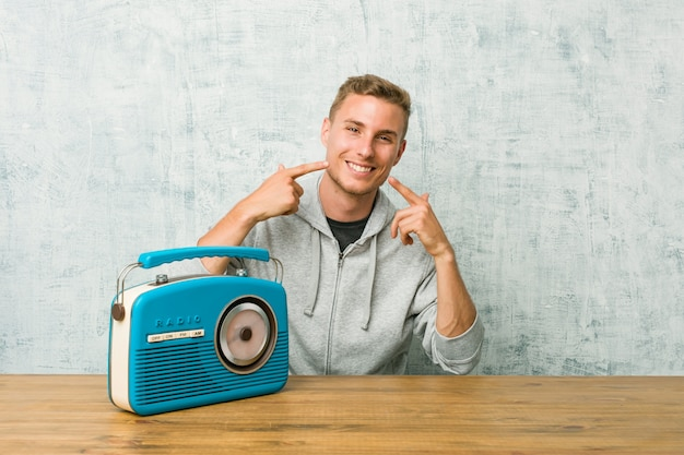 Young man listening to the radio smiles, pointing fingers at mouth