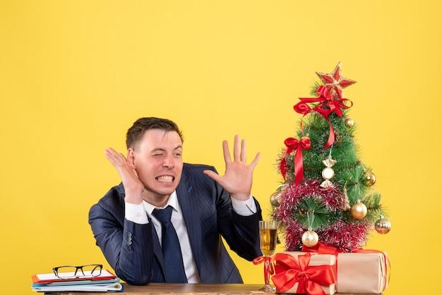 크리스마스 트리 근처 테이블에 앉아 뭔가를 듣고 젊은 남자와 노란색 선물