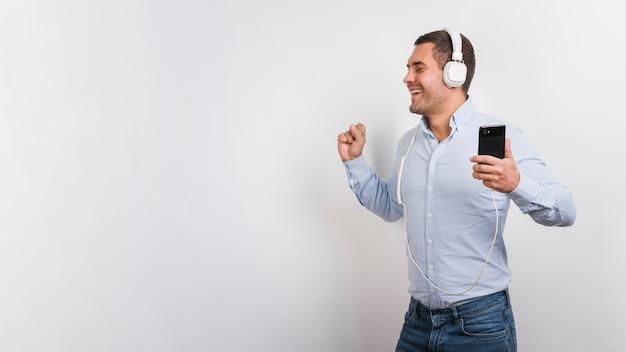 Молодой человек слушает музыку и весело