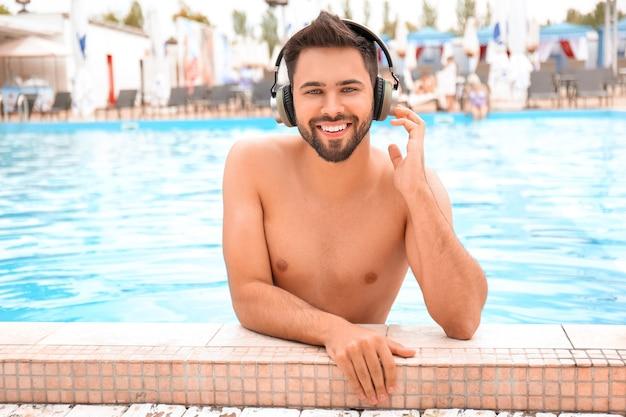 スイミングプールで音楽を聴いている若い男