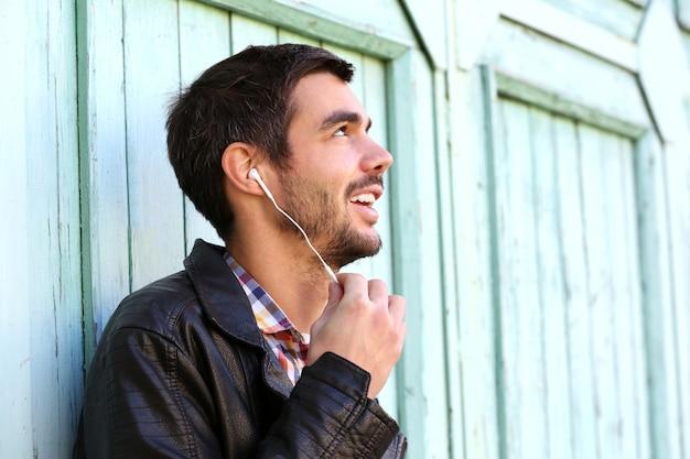 집 벽 배경에서 음악을 듣고 젊은 남자
