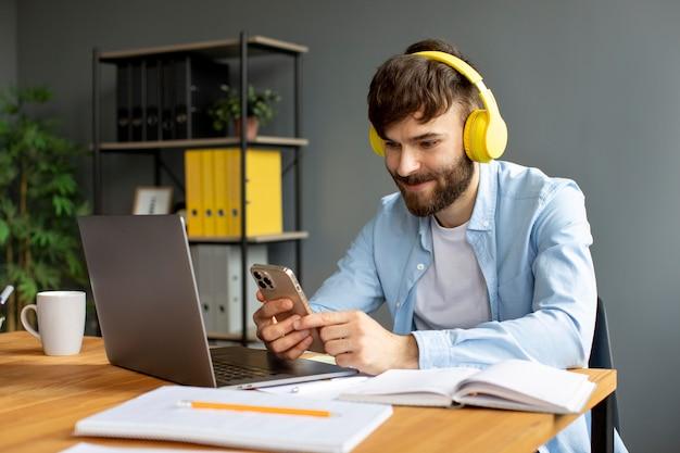 일하는 동안 헤드폰으로 음악을 듣는 청년