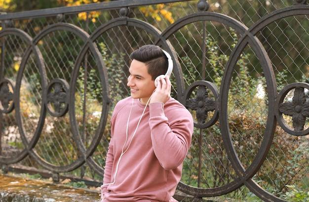 Молодой человек слушает музыку на открытом воздухе