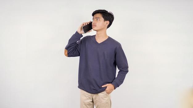Молодой человек слушает что-то на своем мобильном телефоне и чувствует себя смущенным, изолированным на белом фоне