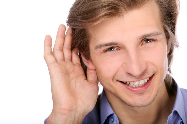 Young man listening with hand on ear