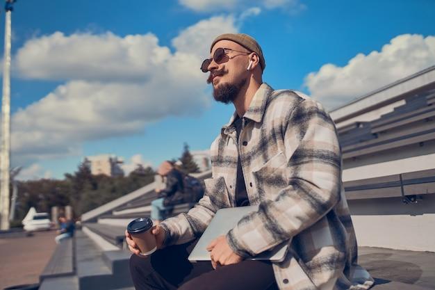 젊은 남자는 헤드폰으로 음악을 듣고 야외에 앉아 노트북과 커피를 손에 들고 있다