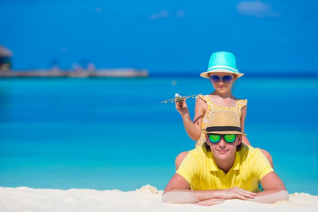 Young man and little girl with miniature of airplane at beach