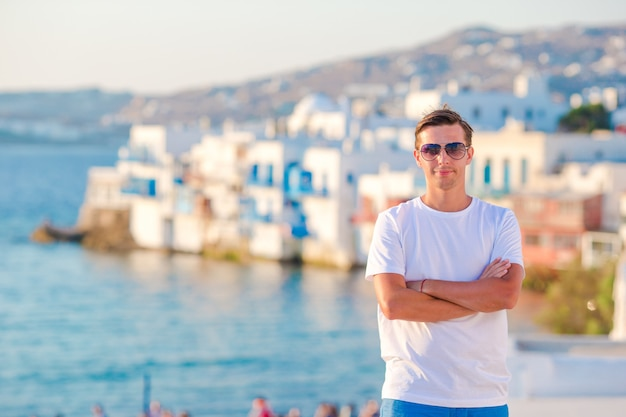 Young man at little venice the most popular tourist area on mykonos island, greece.