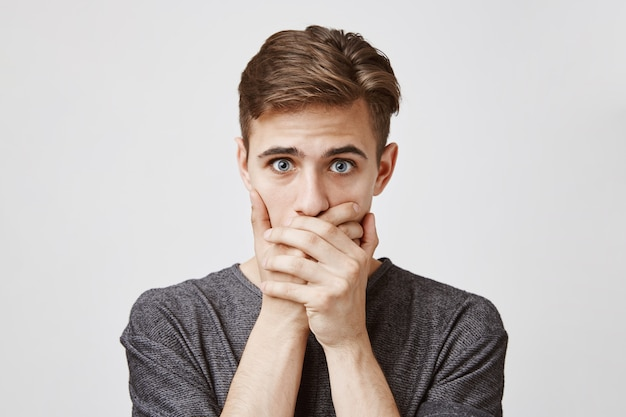 Young man looking afraid, covering his mouth