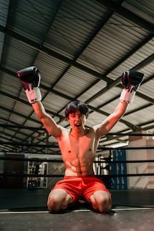 Young man looking aggressive in boxing gloves when winning raises both hands sitting on the floor of the boxing ring