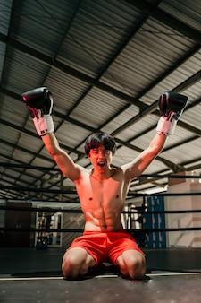 권투 글러브에서 공격적으로 보이는 젊은 남자가 권투 링의 바닥에 앉아 두 손을 올립니다.