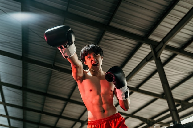 Young man looking aggressive with boxing gloves make a punch motion on boxing ring