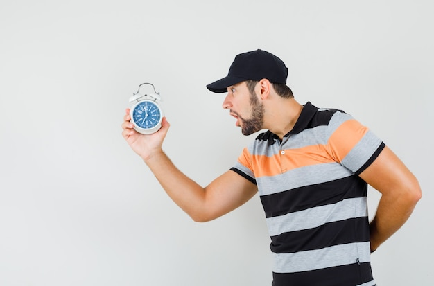 Young man looking at alarm clock in t-shirt, cap and looking agitated .