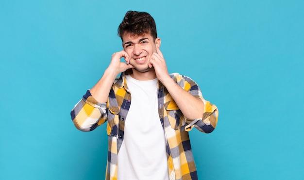 怒り、ストレス、イライラしているように見える若い男は、耳をつんざくような音、音、または大音量の音楽で両耳を覆っています