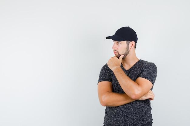 Молодой человек внимательно смотрит в сторону в футболке и кепке и выглядит сосредоточенным