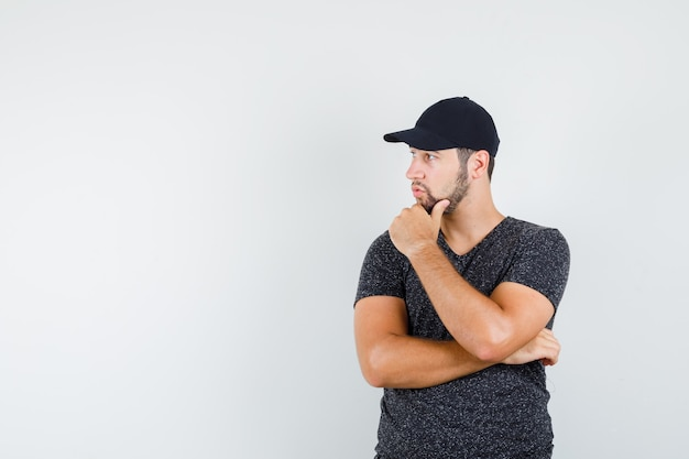 Young man looking aside carefully in t-shirt and cap and looking focused