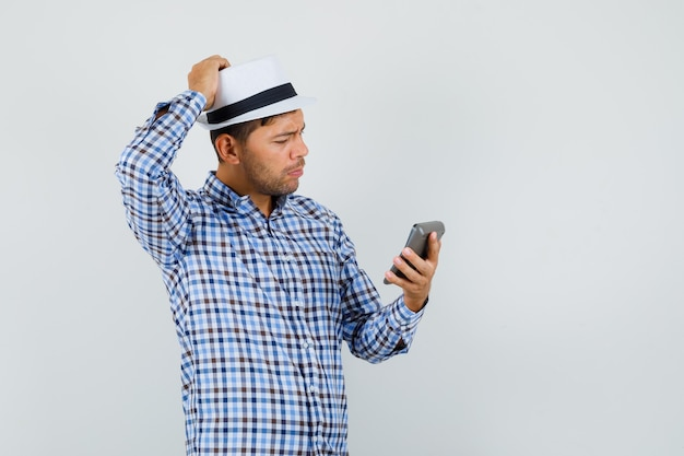 チェックシャツで電卓を見ている若い男