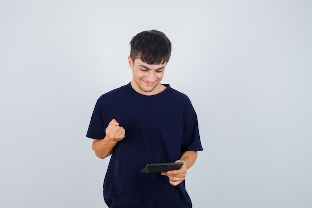 Молодой человек смотрит на калькулятор, показывает жест победителя в черной футболке и выглядит счастливым, вид спереди.