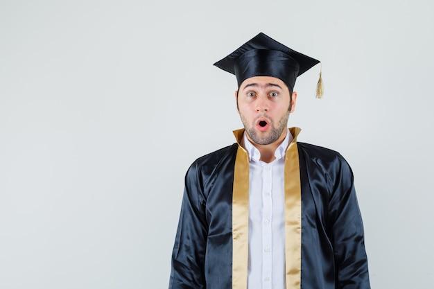 卒業式の制服を着てカメラを見て驚いて見える若い男
