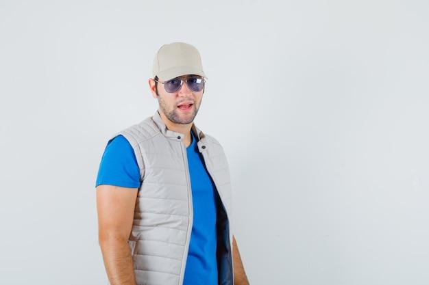 Tシャツ、ジャケット、キャップでカメラを見て、誇らしげに見える若い男。