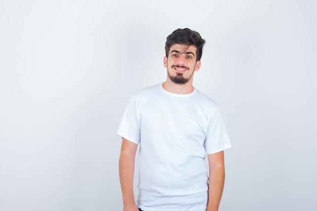 白いtシャツでカメラを見て、エレガントに見える若い男