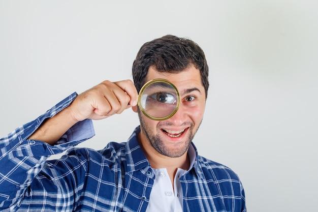 シャツの虫眼鏡を通してカメラを見て、幸せそうに見えて若い男