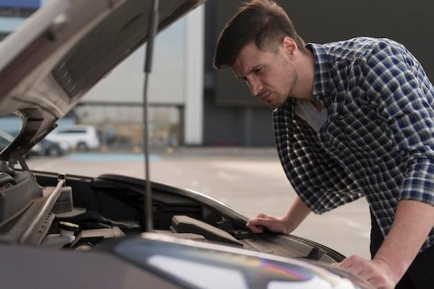 Молодой человек смотрит на машину