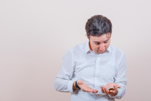 Молодой человек смотрит на долларовую купюру в руке в белой рубашке и выглядит удивленным