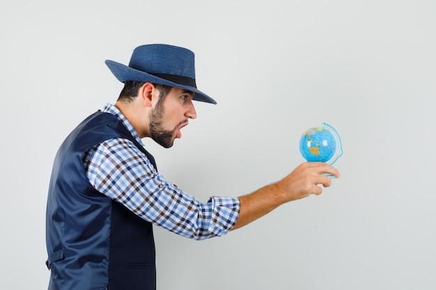 젊은 남자 셔츠, 조끼, 모자에 세계를보고 놀란 찾고.