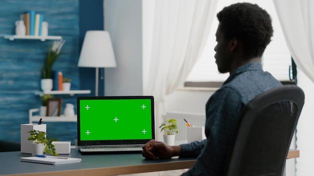녹색 화면을보고 젊은 남자가 밝은 평면에서 노트북 디스플레이를 모의 절연