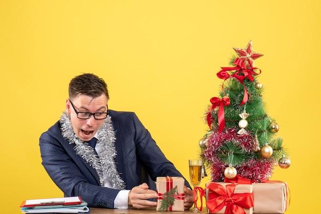 Молодой человек смотрит на свой подарок, сидя за столом возле елки и подарки на желтом
