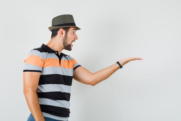 Молодой человек смотрит на его раскинутую ладонь в футболке, шляпе и выглядит удивленным. передний план.