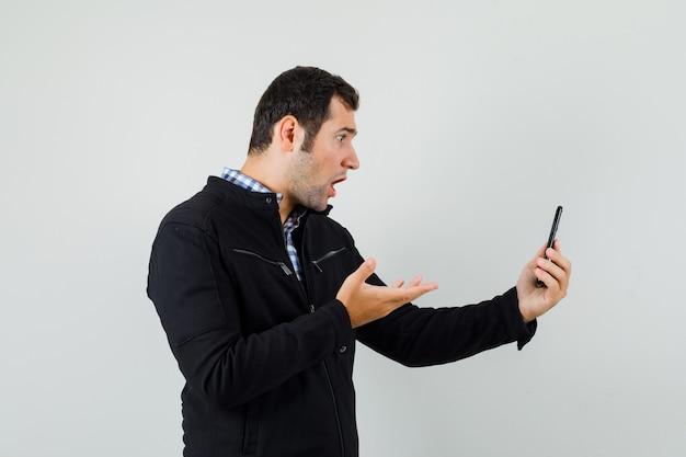 シャツ、ジャケット、ショックを受けた携帯電話を見て若い男