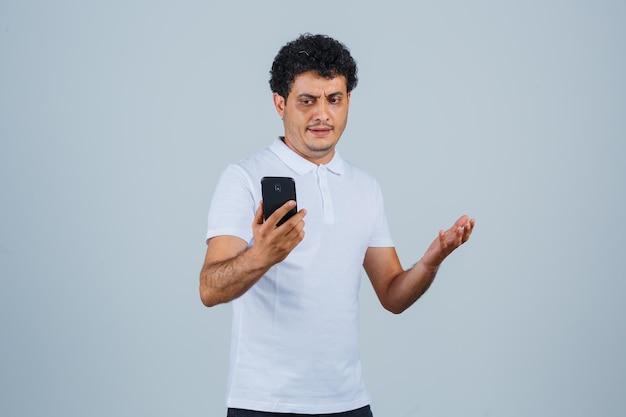 白いtシャツを着て携帯電話を見て、失望した、正面図を見て若い男。