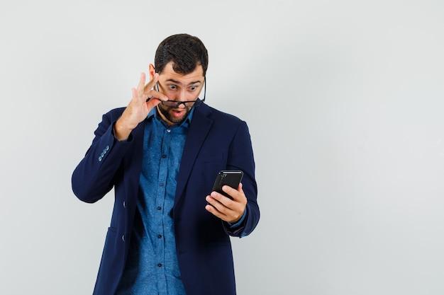 젊은 남자 셔츠, 재킷에 안경을 통해 휴대 전화를보고 충격, 전면보기를 찾고.