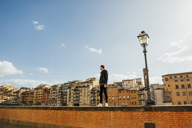 フィレンツェ、トスカーナ、イタリアの旧市街を見ている若い男。