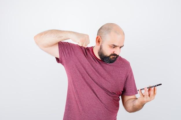 Молодой человек смотрит на телефон и сжимает кулак в розовой футболке и выглядит сердитым. передний план.
