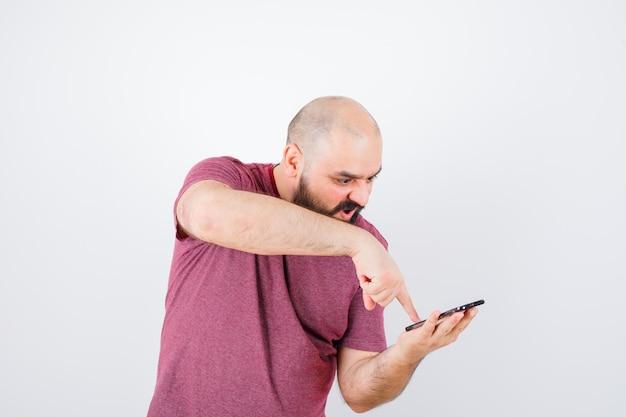 Молодой человек смотрит на телефон и указывая на него указательным пальцем в розовой футболке и выглядит сердитым. передний план.