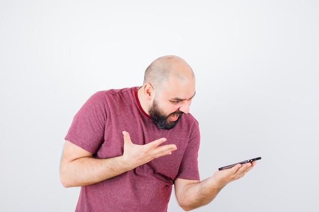 ピンクのtシャツを着て携帯電話を見て、それに向かって手を伸ばして、イライラしている、正面図を見て若い男。 無料写真