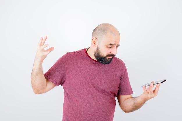 Молодой человек смотрит на телефон в розовой футболке и выглядит раздраженным, вид спереди.