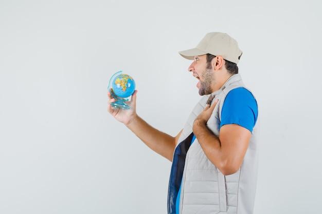 Tシャツ、ジャケット、陽気な顔で学校の地球を見て若い男。