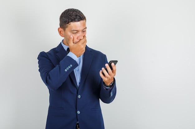 若い男がスーツでスマートフォンを見て、見てみるとビックリ