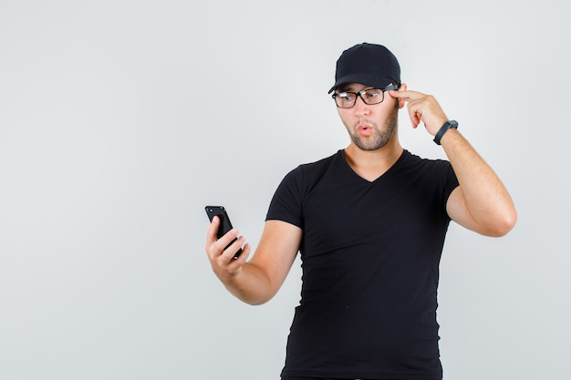 Молодой человек смотрит на смартфон с пальцем на висках в черной футболке