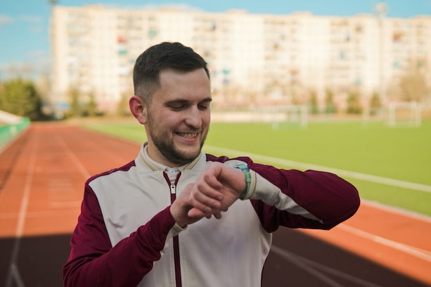 Молодой человек смотрит на умные часы перед бегом на стадионе