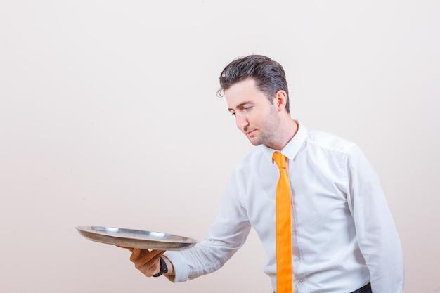 白いシャツのトレイを見て、ネクタイと注意深く見て若い男