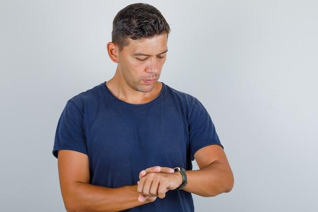 暗い青色のtシャツの手首の時計を見て、時間厳守の正面図を探している若い男。