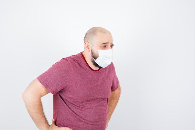 젊은 남자는 분홍색 티셔츠, 마스크를 쓰고 불만족스러워 보이는 허리에 손을 얹고 조심스럽게 시선을 돌립니다.