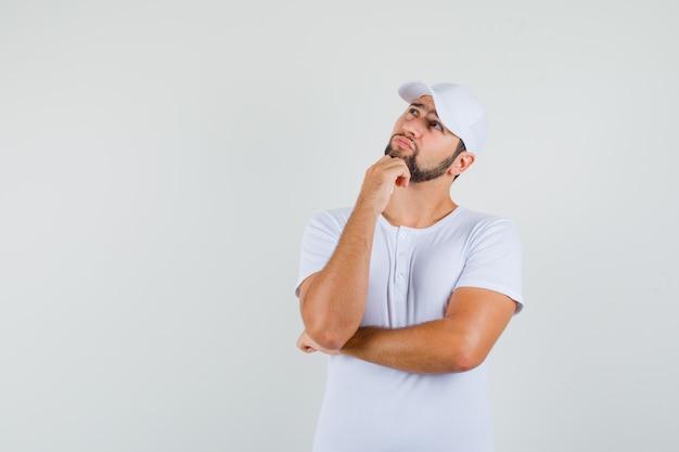 Giovane che guarda lontano mentre si tiene il pugno sulla mascella in maglietta bianca, berretto e guardando pensieroso. vista frontale. spazio per il testo