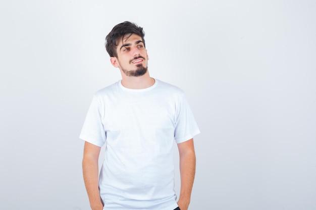 Tシャツに立って、かわいく見えながら目をそらしている若い男